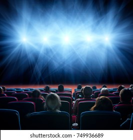 viewers watch line of shining lights at the cinema, long exposure, blue glow