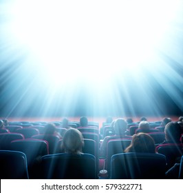 viewers watch shining light at cinema, long exposure, blue glow