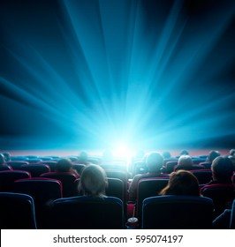 viewers watch shining light at the cinema, long exposure, blue glow
