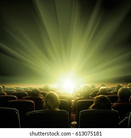 viewers watch shining light at the cinema, long exposure, greenish yellow glow