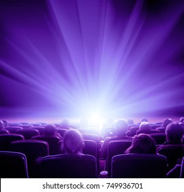viewers watch shining light at the cinema, long exposure, violet glow