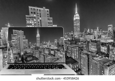 Viewing Manhattan skyline at night on computer screen.