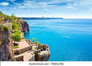 Viewing and resting terrace on slope of cliff near beautiful blue Gulf of Antalya in popular seaside resort city Antalya, Turkey