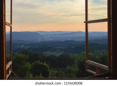 Viewing through old window on village in Serbia, summer season at sunset.