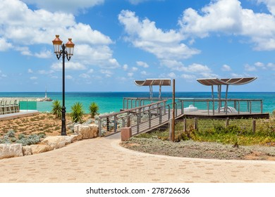 Viewpoint and lamppost on promenade overlooking Mediterranean sea under blue sky with white clouds in Ashqelon, Israel.