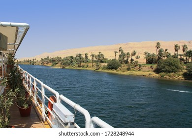 Views from a cruise ship on the eastern bank of the Nile in the day with sunshine. In the foreground the railing and in the background the blue water, the green bank and the mountains of the desert.