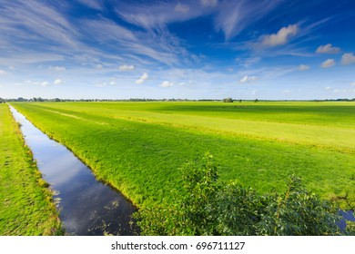 Views of Dutch polder landscape with distant horizon and green meadows with clouds shadow and sunlight spots on the ground surface