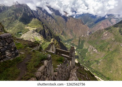 Views over the mountains and rainforest around Machu Picchu citadel from Huayna Picchu summit with some Inca houses on the top of it. An amazing and idyllic view of the Inca trail valleys. Peru