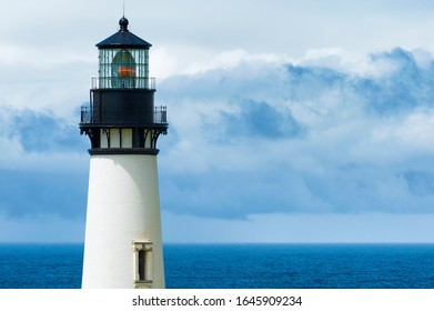 Views of the upper tower of Yaquina Head Lighthouse against cloudy skies over the Pacific Ocean
