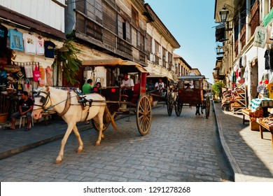 Vigan, Philippines - Feb 26, 2012: The local scene with traditional horse carriages in Calle Crisologo of Vigan City in the province of Ilocos, Philippines.