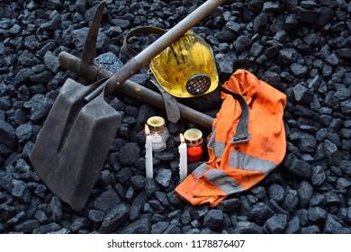 Vigil light, candle with the miner belongings (helmet, pickaxe, shovel, vest, belt) after the fatal accident in the mine