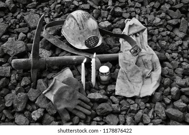 Vigil light, candle with the miner belongings (helmet, gloves, pickaxe, vest, belt) after the fatal accident in the mine, black and white photo