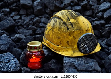 Vigil light, candle with mining helmet on cheap of coal after the fatal accident in the mine
