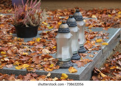 Vigil lights / candles on a grave with autumn leaves