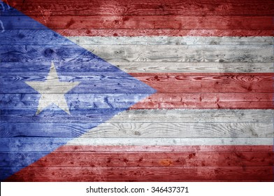 A vignetted background image of the flag of Puerto Rico onto wooden boards of a wall or floor.