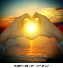 Vignetting Photo of Hands in Heart Shape on the Sunset in the Sea