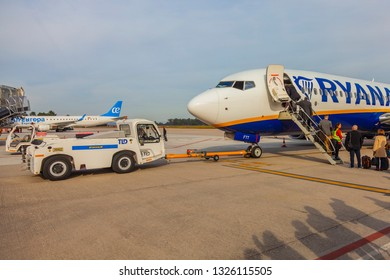 """Vigo / Spain 02 20 2019: Pushback tug with towbar attached with airplane """"Ryanair"""". Ground support equipment in airport."""