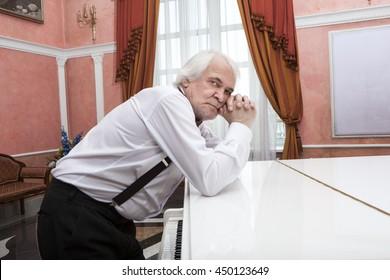 Vigorous charming aging musician playing the white piano