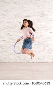 Vigorous girl jumping into air with hula hoop in bright spacious room