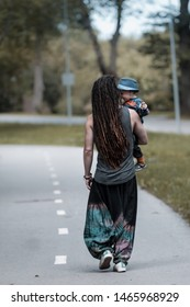 Viimsi/Estonia - 06.20.2018: An athletic rasta man wearing harem pants is walking with his son on a striped light traffic road.