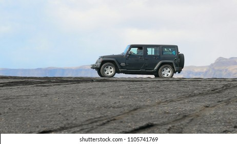 VIK, ICELAND - MAY 03, 2018. Jeep Wrangler Unlimited Sport four wheel drive vehicle being used on terrain on a black sand beach in Iceland