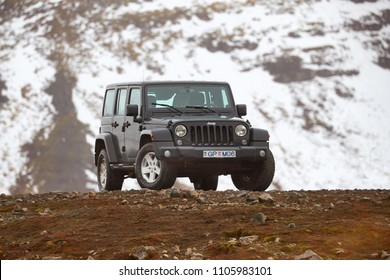 VIK, ICELAND - MAY 03, 2018. Jeep Wrangler Unlimited four wheel drive vehicle on a mountain landscape, snow in background