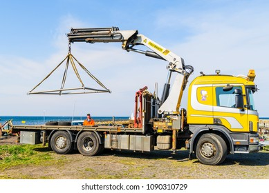 Viken, Sweden - April 30, 2018: Documentary of everyday life and place. Yellow truck lifting a boat launching frame by the coast, using a Palfinger crane.