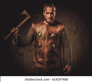 Viking with axes in a traditional warrior clothes