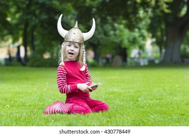 viking blond girl in red shirt in preschool age playing with mobile phone wearing costume hat with horns