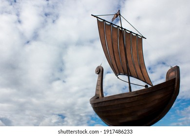 Viking boat copy from the bottom view. Replica of Scandinavian warship drakkar with cloudy blue sky on the background