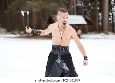 Viking hunter man with an ax screaming in the woods