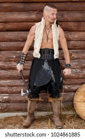 Viking man with an ax in a vest of skin in boots near a wooden wall