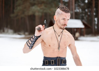Viking man with an ax in the winter forest
