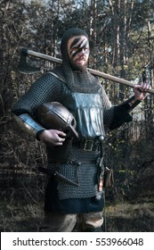 Viking raised his axe on the wild nature background