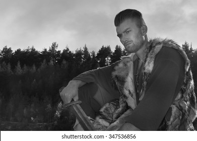 Viking with a sword on a cliff in the mountains