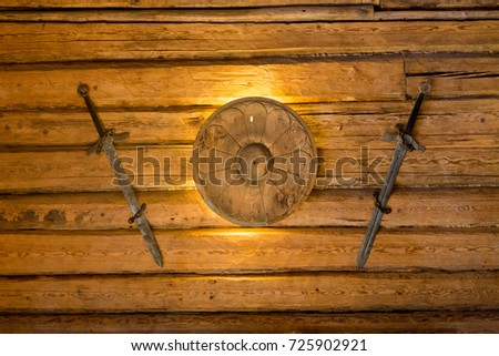 Viking swords and small shield hanging on wooden wall
