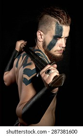Viking with tattoos holding sword on black background