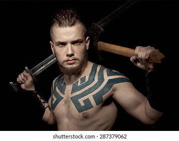 Viking with tattoos on black background with sword and axe in hands.