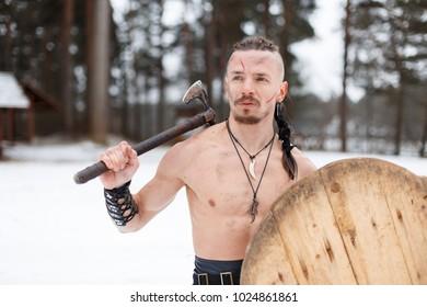 Viking warrior with an ax and shield in a bare torso in the forest