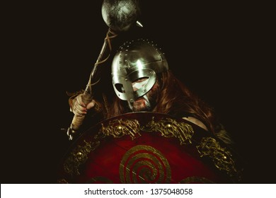 Viking warrior with metallic helmet and animal skins. leather gauntlets, red wooden shield with gold decorations and steel sword