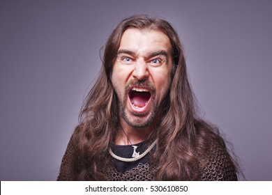 Viking warrior Slavonic man with grivna on the neck, Knight in hauberk on a dark gray background, Ancient Rus Chieftain. Emotional face of a person shouting loudly