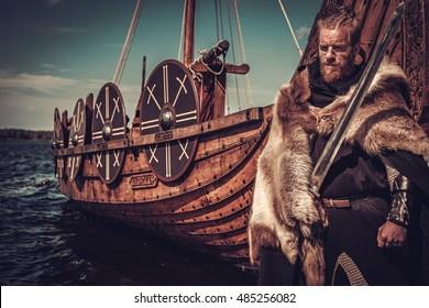 Viking warrior with sword and shield standing near Drakkar on the seashore.