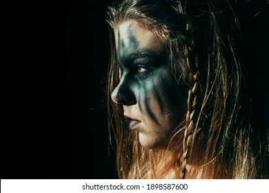 Viking woman, with a fierce look of a shield-maiden and painted face, looking in the darkness with sparks flying