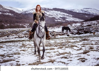 Viking woman with hammer in a traditional warrior clothes. Against the backdrop of a large viking village. A girl with a beautiful gray horse