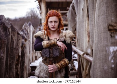 Viking woman with hammer in a traditional warrior clothes. Against the backdrop of a large viking village.