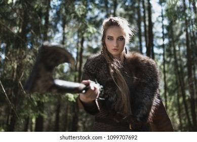 Viking woman with hammer wearing traditional warrior clothes in a deep mysterious forest