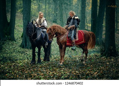 Viking Woman an Man on horses in forest - Vikings riding horse with axes in hands - Medieval movie scene