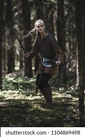Viking woman with sword and hammer wearing traditional warrior clothes in a deep mysterious forest