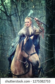 Viking woman warrior with braided hair and painted face riding horse in forest holding shield and ax above head looking dangerous and ready to attack -   Warrior princess - cinematic tone filter