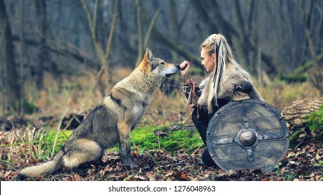 Viking woman warrior with braided hair holding shield close to wild wolf in forest - Outdoor warrior princess alone in woods with wolf – movie theme - cinematic tone filter
